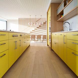 Ejemplo de cocina de galera, moderna, de tamaño medio, abierta, con fregadero bajoencimera, armarios con paneles lisos, puertas de armario amarillas, encimera de acrílico, salpicadero blanco, electrodomésticos de acero inoxidable, suelo de madera clara, una isla y encimeras blancas