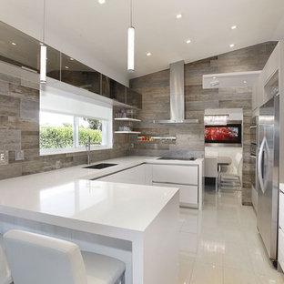 マイアミの中サイズのコンテンポラリースタイルのおしゃれなキッチン (アンダーカウンターシンク、フラットパネル扉のキャビネット、白いキャビネット、人工大理石カウンター、シルバーの調理設備の、リノリウムの床) の写真