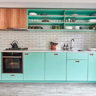ロンドンの中サイズの北欧スタイルのおしゃれなキッチン (アンダーカウンターシンク、ターコイズのキャビネット、人工大理石カウンター、白いキッチンパネル、サブウェイタイルのキッチンパネル、磁器タイルの床、アイランドなし、グレーの床、白いキッチンカウンター、オープンシェルフ) の写真