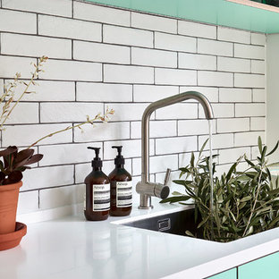 This is an example of a mid-sized scandinavian l-shaped eat-in kitchen in London with an undermount sink, flat-panel cabinets, turquoise cabinets, solid surface benchtops, white splashback, subway tile splashback, panelled appliances, porcelain floors, no island, grey floor and white benchtop.