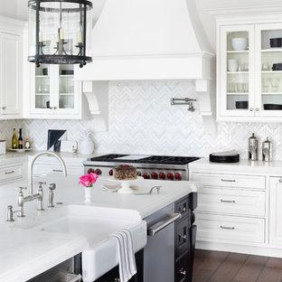 Klassische Küche in L-Form mit weißen Schränken, Küchengeräten aus Edelstahl, Kücheninsel, braunem Boden, Landhausspüle, Glasfronten, bunter Rückwand und dunklem Holzboden in Miami