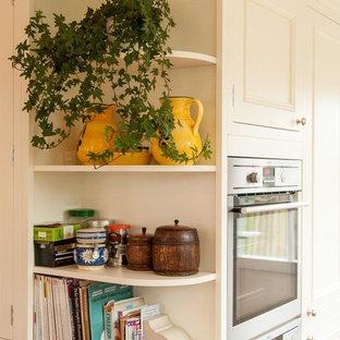 Esempio di una cucina minimal di medie dimensioni con lavello da incasso, ante in stile shaker, ante beige, top in granito, paraspruzzi nero, paraspruzzi con piastrelle in ceramica, elettrodomestici in acciaio inossidabile, pavimento in ardesia, penisola e pavimento arancione