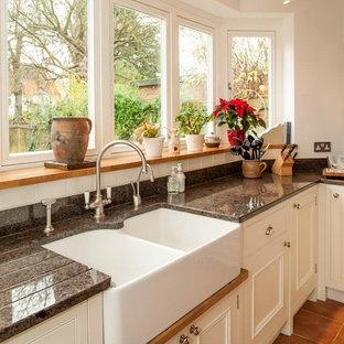 Immagine di una cucina design di medie dimensioni con lavello da incasso, ante in stile shaker, ante beige, top in granito, paraspruzzi nero, paraspruzzi con piastrelle in ceramica, elettrodomestici in acciaio inossidabile, pavimento in ardesia, penisola e pavimento arancione