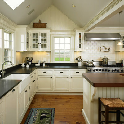 Example of a large cottage l-shaped medium tone wood floor open concept kitchen design in Boston with a farmhouse sink, glass-front cabinets, white cabinets, white backsplash, subway tile backsplash, stainless steel appliances, an island and black countertops