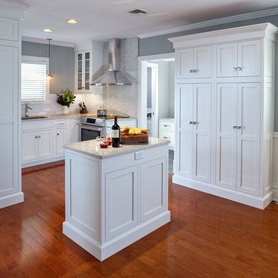Inspiration for a small craftsman u-shaped medium tone wood floor eat-in kitchen remodel in Other with an undermount sink, shaker cabinets, white cabinets, quartz countertops, white backsplash, porcelain backsplash, stainless steel appliances and an island