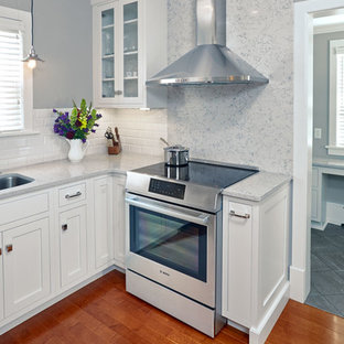 Small arts and crafts u-shaped eat-in kitchen in Other with an undermount sink, shaker cabinets, white cabinets, quartz benchtops, white splashback, porcelain splashback, stainless steel appliances, medium hardwood floors and with island.