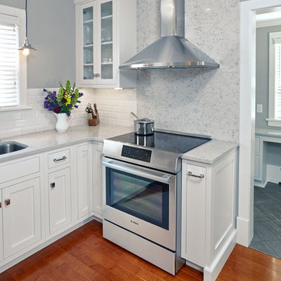 Example of a small arts and crafts u-shaped medium tone wood floor eat-in kitchen design in Other with an undermount sink, shaker cabinets, white cabinets, quartz countertops, white backsplash, porcelain backsplash, stainless steel appliances and an island
