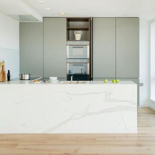 Diseño de cocina en U, contemporánea, pequeña, con armarios con paneles lisos, salpicadero de vidrio templado, suelo de madera clara, fregadero bajoencimera, puertas de armario verdes y península