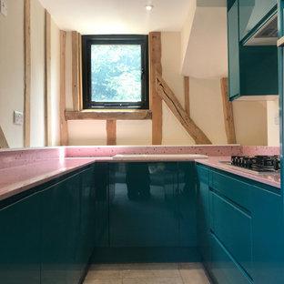 Modelo de cocina moderna, pequeña, con armarios con paneles lisos, puertas de armario azules, encimera de vidrio reciclado, electrodomésticos de acero inoxidable y encimeras rosas