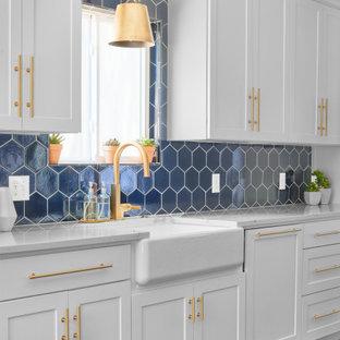 Einzeilige, Große Klassische Wohnküche mit weißen Schränken, Küchenrückwand in Blau, Rückwand aus Keramikfliesen, Kücheninsel, grauem Boden und weißer Arbeitsplatte in Austin
