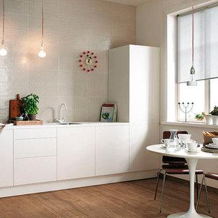 Modelo de cocina comedor lineal, minimalista, pequeña, sin isla, con fregadero encastrado, armarios con paneles lisos, puertas de armario blancas, encimera de laminado, salpicadero beige, salpicadero de azulejos de cerámica, electrodomésticos blancos y suelo de baldosas de porcelana