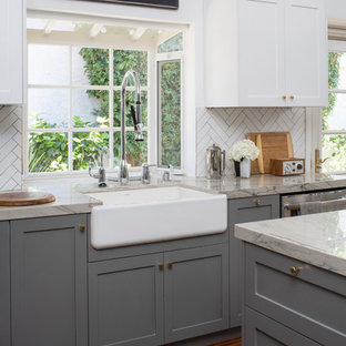 Design ideas for a medium sized classic u-shaped kitchen pantry in Los Angeles with a belfast sink, shaker cabinets, grey cabinets, engineered stone countertops, white splashback, porcelain splashback, stainless steel appliances, medium hardwood flooring and an island.