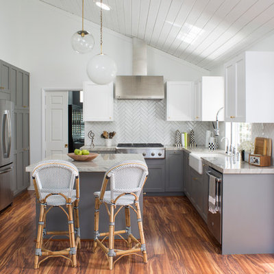 Kitchen - mid-sized country u-shaped medium tone wood floor kitchen idea in Los Angeles with a farmhouse sink, shaker cabinets, gray cabinets, quartz countertops, white backsplash, porcelain backsplash, stainless steel appliances and an island