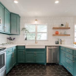 Ispirazione per un'ampia cucina ad U minimalista con lavello stile country, ante in stile shaker, ante blu, paraspruzzi bianco, elettrodomestici in acciaio inossidabile, nessuna isola e pavimento nero
