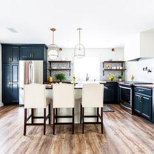 Offene, Mittelgroße Country Küche in L-Form mit Landhausspüle, profilierten Schrankfronten, blauen Schränken, Arbeitsplatte aus Holz, Küchenrückwand in Blau, Rückwand aus Zementfliesen, Küchengeräten aus Edelstahl, Laminat, Kücheninsel, braunem Boden und brauner Arbeitsplatte in Los Angeles
