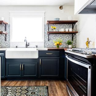 Inspiration för ett mellanstort lantligt brun brunt kök, med en rustik diskho, luckor med upphöjd panel, blå skåp, träbänkskiva, blått stänkskydd, stänkskydd i cementkakel, rostfria vitvaror, laminatgolv, en köksö och brunt golv
