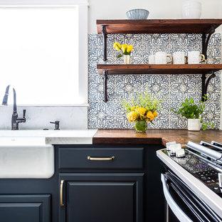 Bild på ett mellanstort lantligt brun brunt kök, med en rustik diskho, luckor med upphöjd panel, blå skåp, träbänkskiva, blått stänkskydd, stänkskydd i cementkakel, rostfria vitvaror, laminatgolv, en köksö och brunt golv