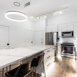 ダラスの小さいモダンスタイルのおしゃれなキッチン (フラットパネル扉のキャビネット、白いキャビネット、白いキッチンパネル、シルバーの調理設備の、クッションフロア、茶色い床、白いキッチンカウンター、アンダーカウンターシンク、ガラスカウンター、磁器タイルのキッチンパネル) の写真