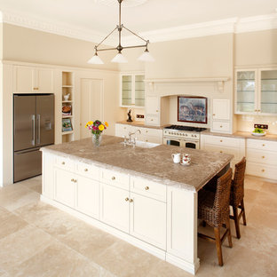 Inspiration for a mid-sized timeless galley travertine floor eat-in kitchen remodel in Sydney with glass-front cabinets, a farmhouse sink, white appliances, marble countertops and an island