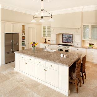 Cette photo montre une cuisine américaine parallèle chic de taille moyenne avec un placard à porte vitrée, un évier de ferme, un électroménager blanc, un sol en travertin, un plan de travail en marbre et un îlot central.