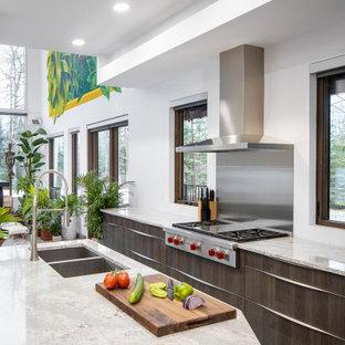 Modelo de cocina de galera, contemporánea, con fregadero bajoencimera, armarios con paneles lisos, puertas de armario de madera en tonos medios, electrodomésticos de acero inoxidable, una isla y encimeras grises