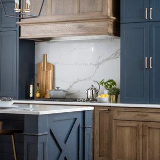 ボストンの中サイズのカントリー風おしゃれなキッチン (エプロンフロントシンク、フラットパネル扉のキャビネット、青いキャビネット、クオーツストーンカウンター、白いキッチンパネル、石スラブのキッチンパネル、シルバーの調理設備の、無垢フローリング、茶色い床、白いキッチンカウンター) の写真