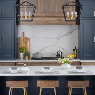 Свежая идея для дизайна: кухня-гостиная среднего размера в стиле кантри с раковиной в стиле кантри, плоскими фасадами, синими фасадами, столешницей из кварцевого агломерата, белым фартуком, фартуком из каменной плиты, техникой из нержавеющей стали, паркетным полом среднего тона, островом, коричневым полом и коричневой столешницей - отличное фото интерьера