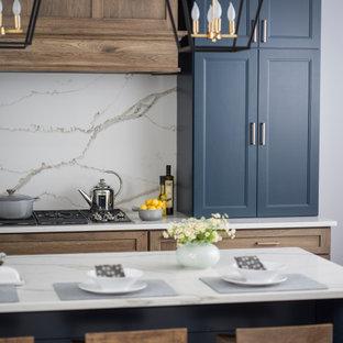 グランドラピッズの中くらいのカントリー風おしゃれなキッチン (エプロンフロントシンク、フラットパネル扉のキャビネット、青いキャビネット、クオーツストーンカウンター、白いキッチンパネル、石スラブのキッチンパネル、シルバーの調理設備、無垢フローリング、茶色い床、白いキッチンカウンター) の写真