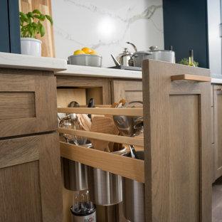Foto på ett mellanstort lantligt vit kök, med en rustik diskho, släta luckor, skåp i ljust trä, bänkskiva i kvartsit, vitt stänkskydd, stänkskydd i sten, rostfria vitvaror, mellanmörkt trägolv, en köksö och brunt golv