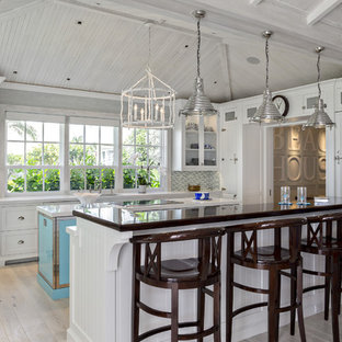 Coastal kitchen designs - Inspiration for a coastal l-shaped light wood floor and gray floor kitchen remodel in Miami with recessed-panel cabinets, white cabinets, multicolored backsplash, mosaic tile backsplash, an island and white countertops