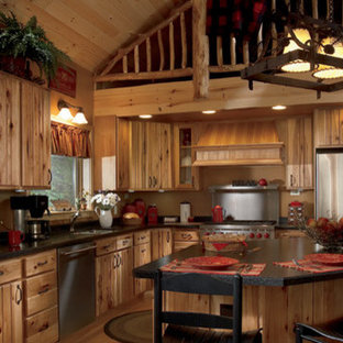 Photo of a large farmhouse l-shaped enclosed kitchen in Las Vegas with a double-bowl sink, louvered cabinets, medium wood cabinets, soapstone worktops, light hardwood flooring and an island.