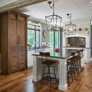 Mid-sized transitional l-shaped kitchen in Philadelphia with a farmhouse sink, medium hardwood floors, with island, raised-panel cabinets, white cabinets, black splashback, glass tile splashback and stainless steel appliances.