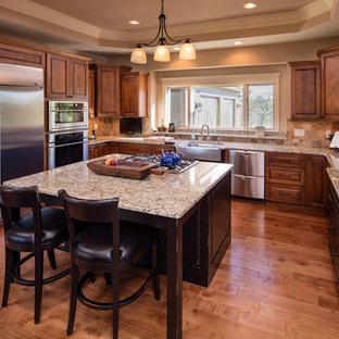 Design ideas for a large traditional u-shaped eat-in kitchen in Chicago with a farmhouse sink, raised-panel cabinets, medium wood cabinets, granite benchtops, brown splashback, slate splashback, stainless steel appliances, medium hardwood floors, with island and brown floor.