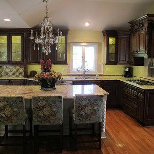 他の地域のヴィクトリアン調のおしゃれなキッチン (ダブルシンク、濃色木目調キャビネット、大理石カウンター、白いキッチンパネル、シルバーの調理設備、無垢フローリング、レイズドパネル扉のキャビネット) の写真