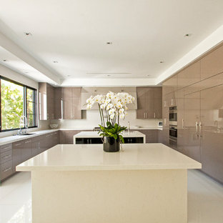 Expansive modern u-shaped eat-in kitchen in Los Angeles with an undermount sink, flat-panel cabinets, beige cabinets, solid surface benchtops, stainless steel appliances, marble floors and multiple islands.