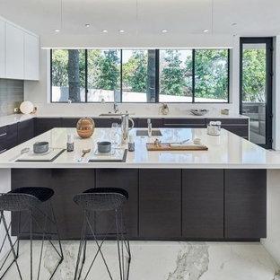 Diseño de cocina en L, moderna, grande, abierta, con fregadero bajoencimera, armarios con paneles lisos, puertas de armario blancas, encimera de cuarcita, salpicadero verde, electrodomésticos de acero inoxidable, suelo de mármol, una isla y suelo blanco