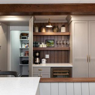 シカゴの中くらいのカントリー風おしゃれなキッチン (アンダーカウンターシンク、シェーカースタイル扉のキャビネット、グレーのキャビネット、クオーツストーンカウンター、黄色いキッチンパネル、セラミックタイルのキッチンパネル、シルバーの調理設備、無垢フローリング、茶色い床、白いキッチンカウンター、表し梁) の写真