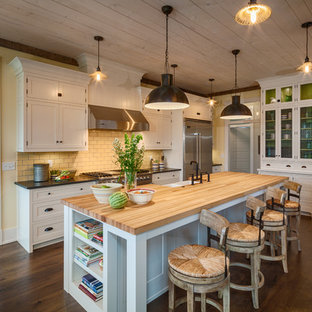 Photo of a mid-sized country l-shaped open plan kitchen in Other with a farmhouse sink, shaker cabinets, white cabinets, wood benchtops, beige splashback, porcelain splashback, stainless steel appliances, dark hardwood floors, with island and brown floor.