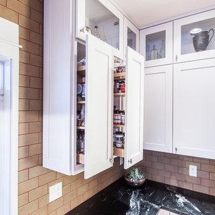 Exempel på ett avskilt, mellanstort lantligt svart svart l-kök, med en rustik diskho, skåp i shakerstil, vita skåp, bänkskiva i täljsten, grönt stänkskydd, stänkskydd i keramik, rostfria vitvaror, ljust trägolv, en köksö och gult golv