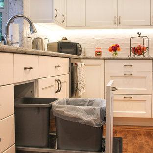 Aménagement d'une grande cuisine américaine classique en U avec un évier encastré, un placard à porte shaker, des portes de placard blanches, un plan de travail en granite, une crédence blanche, une crédence en carrelage métro, un électroménager en acier inoxydable, un sol en bois brun, un îlot central, un sol marron et un plan de travail blanc.