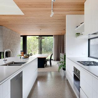 Idée de décoration pour une cuisine ouverte parallèle design avec un évier 2 bacs, un placard à porte plane, des portes de placard blanches, un électroménager en acier inoxydable, béton au sol et un sol gris.
