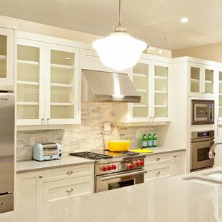 Réalisation d'une arrière-cuisine linéaire de taille moyenne avec un évier 3 bacs, un placard à porte vitrée, des portes de placard blanches, une crédence grise, un électroménager en acier inoxydable et un îlot central.