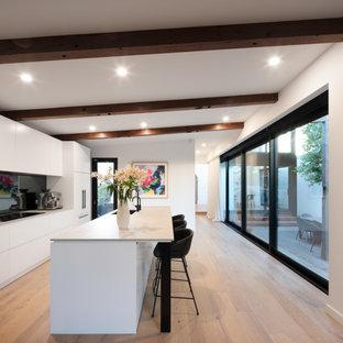 メルボルンの広いコンテンポラリースタイルのおしゃれなキッチン (ドロップインシンク、フラットパネル扉のキャビネット、白いキャビネット、メタリックのキッチンパネル、ミラータイルのキッチンパネル、シルバーの調理設備、淡色無垢フローリング、茶色い床、ベージュのキッチンカウンター) の写真
