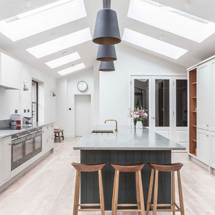 Classic kitchen in West Midlands with a submerged sink, shaker cabinets, grey cabinets, light hardwood flooring, an island, beige floors and grey worktops.