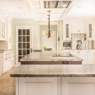 Geräumige Klassische Wohnküche in U-Form mit Landhausspüle, Kassettenfronten, weißen Schränken, Granit-Arbeitsplatte, bunter Rückwand, Rückwand aus Mosaikfliesen, Elektrogeräten mit Frontblende, Travertin, Halbinsel, beigem Boden und brauner Arbeitsplatte in Boston