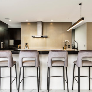 Photo of a large contemporary u-shaped kitchen in Melbourne with beige splashback, black appliances, marble floors, white floor, flat-panel cabinets, black cabinets and a peninsula.