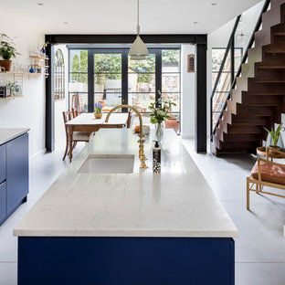Пример оригинального дизайна: большая линейная кухня в классическом стиле с кладовкой, накладной раковиной, фасадами с утопленной филенкой, синими фасадами, гранитной столешницей, фартуком из зеркальной плитки, техникой из нержавеющей стали, полом из керамической плитки, островом и серым полом