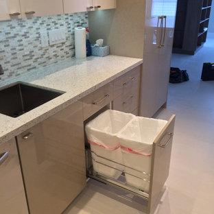 マイアミの中サイズのモダンスタイルのおしゃれなキッチン (アンダーカウンターシンク、フラットパネル扉のキャビネット、白いキャビネット、再生ガラスカウンター、グレーのキッチンパネル、ガラスタイルのキッチンパネル、シルバーの調理設備の、磁器タイルの床) の写真