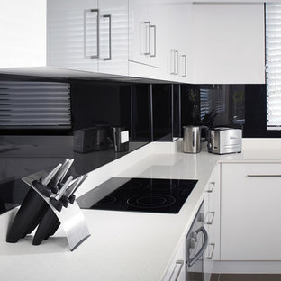 Example of a trendy kitchen design in Columbus with flat-panel cabinets and glass sheet backsplash