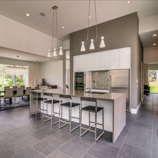 Mid-sized modern eat-in kitchen inspiration - Mid-sized minimalist single-wall travertine floor eat-in kitchen photo in Nashville with a single-bowl sink, flat-panel cabinets, white cabinets, solid surface countertops, mosaic tile backsplash, stainless steel appliances and an island